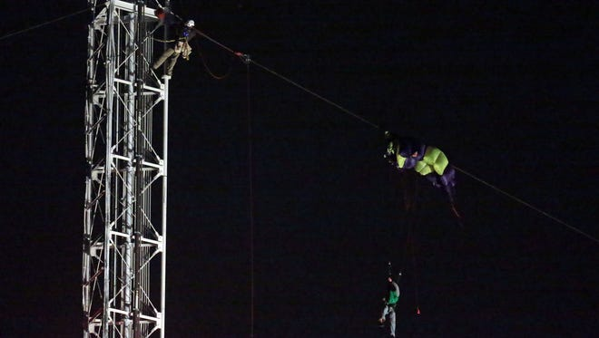 An emergency worker (top left) begins a rescue attempt to save a parachutist dangling from a broadcast tower in south St. Louis County, Mo.