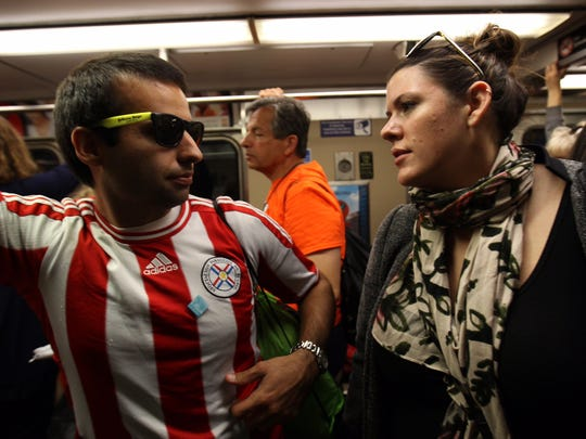 Caitlin Grant, of Wilmington, and Fabian Barua, of Paraguay, ride Septa into Philadelphia to see Pope Francis.