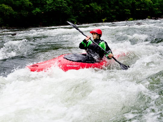 A kayaker paddles through a rapid during a whitewater