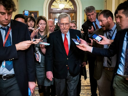 Reporters trail Republican Senate Majority Leader from Kentucky Mitch McConnell (C) while walking through the US Capitol after he met with US President Donald J. Trump over the budget stalemate.
