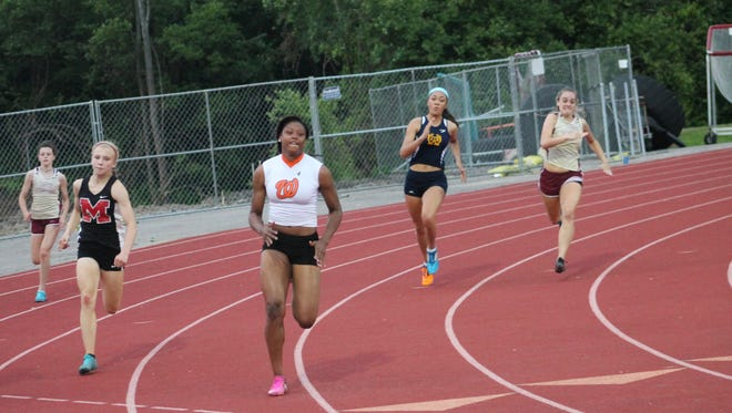 Doneasha Brewer of Withrow churns through the 200 meters at the ECC meet ahead of Milford's Andrea Armstrong (left).