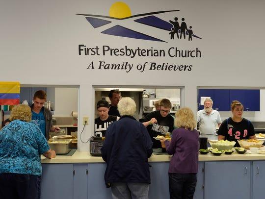 Volunteers serve dinner to members of the community