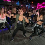 Jessie Diaz, center, form New York City, participates in a Vixen Workout fitness concert, at the Highline Ballroom, in New York, Saturday, July 26, 2014. Former Miami Heat dancer Janet Jones created the Vixen Workout two years ago after she lost her job as a financial assistant and her high-energy routine has caught on in New York and other cities. (AP Photo/Richard Drew)