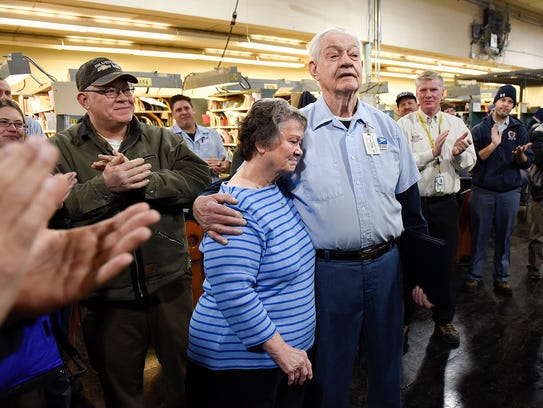 Postal carrier Ray Lund, 79, gets a hug from his wife