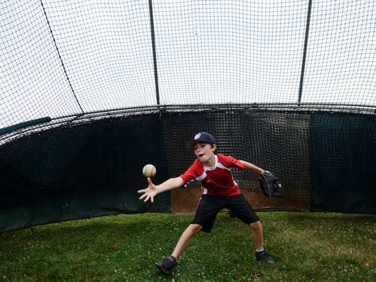 Andrew Srebroski, 10, of York Haven, tosses the ball with Branstin Shue, 10, of Dover, not pictured, on the sidelines during a Central League baseball game at Mount Wolf Tuesday, July 9, 2013.  DAILY RECORD/SUNDAY NEWS - KATE PENN