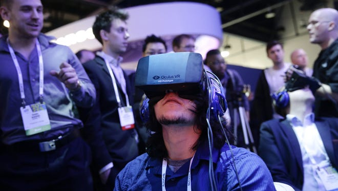 Visitors use Oculus Rift virtual reality headsets at the International Consumer Electronics Show.