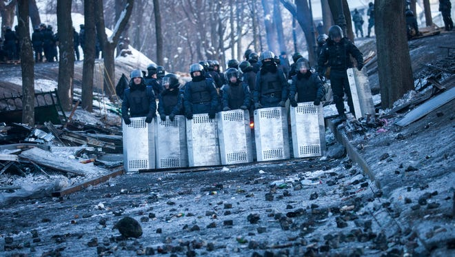Ukrainian police block a street from anti-government protesters Monday in Kiev.