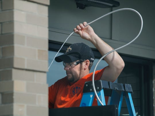 Mike Conover of Hilton, with Bethany Technologies, works on the electrical supply to the front doors of the new location for the East Rochester village office at the Eyer building in East Rochester, N.Y. on Thursday, September 11 2014.