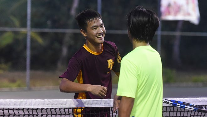 Father Duenas teammates Camden Camacho, 16, left, and Gabriel Tan, 16, meet at the net after their Independent Interscholastic Athletic Association of Guam Tennis League Boys' Singles Finals match at the Rick Ninete Tennis Center in Hagåtña on March 13, 2018. Camacho won the match 8-2.
