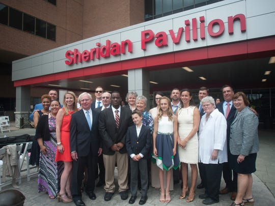 Members of the Sheridan  family pose for a portrait near the new named building, Cooper Sheridan Pavilion  in honor of late CEO John Sheridan and his Joyce.