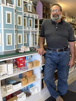 Tom Leone, owner of Lilliput Dollhouses and Miniatures in Fairport, stands next to a dollhouse he is refurbishing.