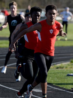 Richmond's Noah Shaw hands the baton to Sid Sagna in the 4x100m relay against Greenville Thursday, April 14, 2016, in a track and field meet at RHS.