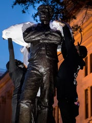 Protesters cover the Sam Davis monument with a white