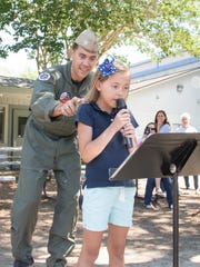 Navy Lt. Mason sneaks up behind his daughter Rhys as she sings the National Anthem at the Creative Learning Center in Pensacola on Friday, May 26, 2017.  Hoyt timed his leave from Saudi Arabia to surprise his seven-year-old daughter Rhys on her last day of school.