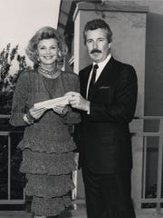 Barbara Sinatra receives a $15,000 check from Ken Rizotto
