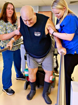 Rehab Aide Sara Soler, left, and  Physical Therapist Assistant Tasha Barcikowski, right, work with resident Robert Brenner, 73, as he demonstrates the strength he has gained through physical therapy as Pleasant Acres introduces their new, larger rehabilitation gym at the facility in Springettsbury Township, Tuesday, Feb. 20, 2018. Brenner has been a resident since May of 2010 after he suffered a stroke. Dawn J. Sagert photo