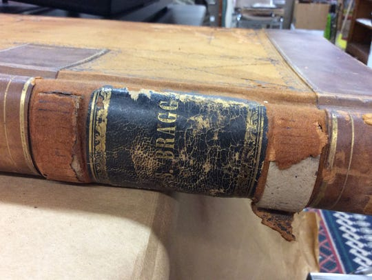 The spine of an old leather bound book buried in a