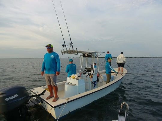 Capt. Ryan  Kane, left, helps the Fish N Chips 2 team search for tarpon.