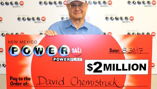 David Chemistruck of Edgewood, New Mexico, poses with the oversized $2 million check he won playing Powerball.