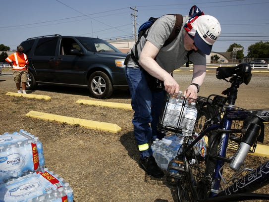 Jeff Rhodes of Salem loads bottled water into his bicycle