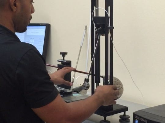 A technician drop a weight into a golf club face to measure the bounce-back of the face at the KGZ Preforrmance Center in Palm Desert