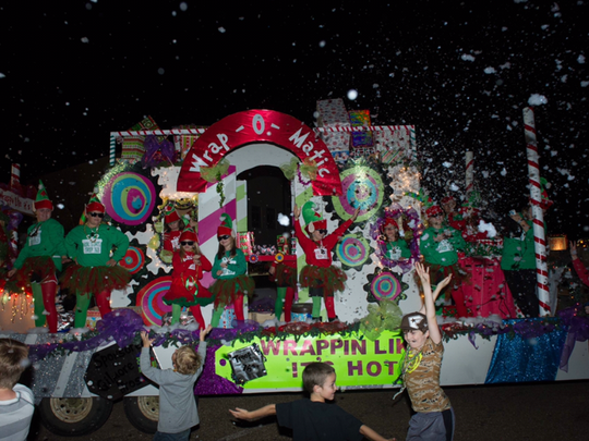 """Children dance next to the """"Wrap-o-Matic"""" float in the 2014 Brandon Christmas parade."""