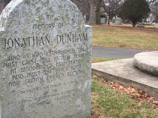 A memorial for Jonathan Singletary Dunham next to a portion of the first gristmill in New Jersey sits outside Dunham's house, now the rectory for Trinity Episcopal Church.