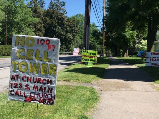 Residents along South Main Street in Pittsford display signs in opposition to the proposed cell tower.