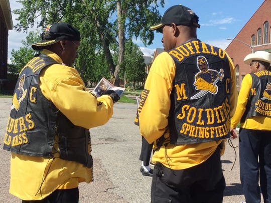 Members of the Springfield, Massachusetts chapter of the Buffalo Soldiers Motorcycle Club look through a pamphlet before a ceremony inaugurating a new Vermont historic marker for the Vermont African American Heritage Trail at Fort Ethan Allen in Colchester on Sunday, July 2, 2017.