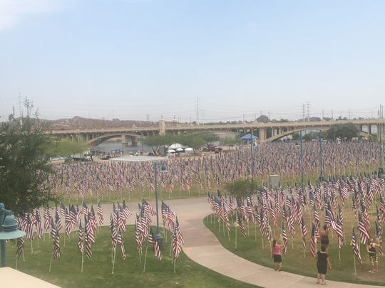 Volunteers returned to Tempe Beach Park Friday morning to erect flags to honor the victims of the Sept. 11, 2001, terror attacks at the 14th annual Tempe Healing Field. Alexis Egeland/The Republic