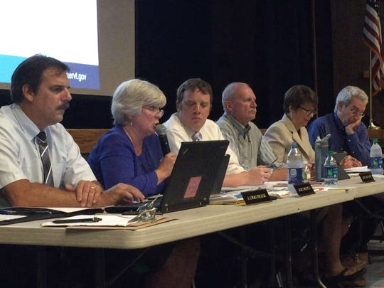 Colchester Town Manager Dawn Francis, second from left, speaks during a public hearing on whether the town should be responsible for plowing private roads on Tuesday, Sept. 12, 2017, at Colchester High School. Other town employees and members of the Colchester Selectboard heard feedback from residents.