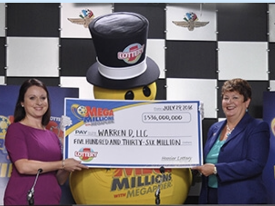 Lauren Littlefield, left, a spokeswoman for the unidentified family that won a $536 million Mega Millions drawing in Indiana in 2016, poses with a ceremonial check with Executive Director of the Hoosier Lottery Sarah M. Taylor.