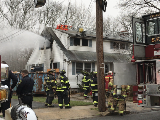 Firefighters spraying water outside of the second story