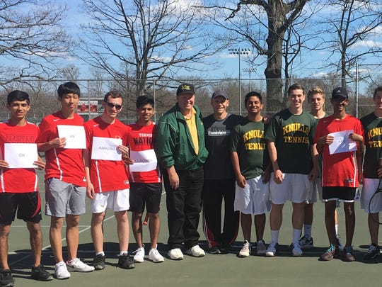 Parsippany tennis players hold up signs in honor of Morris Knolls coach Dan Benz's upcoming retirement before their match on April 26.