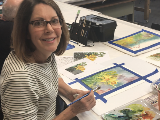 Carrie Brazell works in watercolors during a class