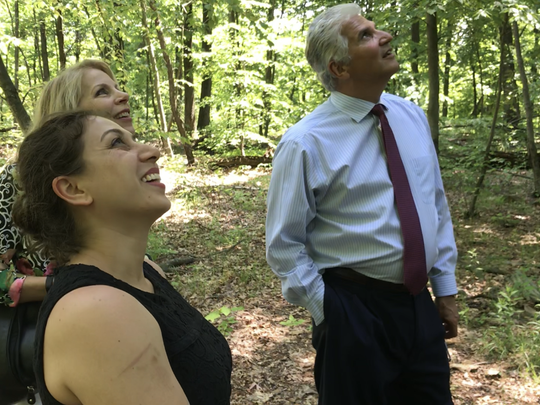 "Montclair artist Asha Ganpat, founder of the South Mountain Wildflower Sculpture Park Tricia Zimic and Essex County Executive Joseph DiVincenzo Jr., from left, loop up at the sculpture ""Soothsayer"" a series of about 35 windchimes attached to a dead tree on Tuesday, May 29, 2018."