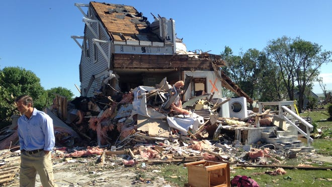Sen. John Thune on Friday tours a Wessington Springs neighborhood where a tornado damaged homes earlier this week.