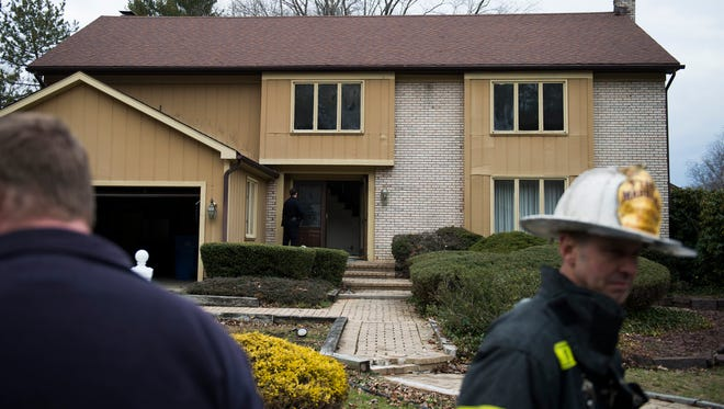 Police and fire personnel work the scene of a house fire Tuesday on the 1000 block of Red Oak Road in Cherry Hill.