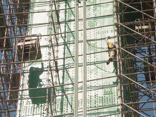 Painters climb scaffolds and stand in baskets to paint