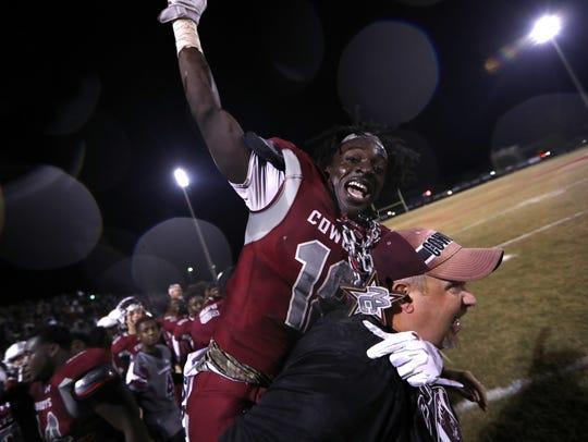 Madison County's Travis Jay celebrates on the sidelines