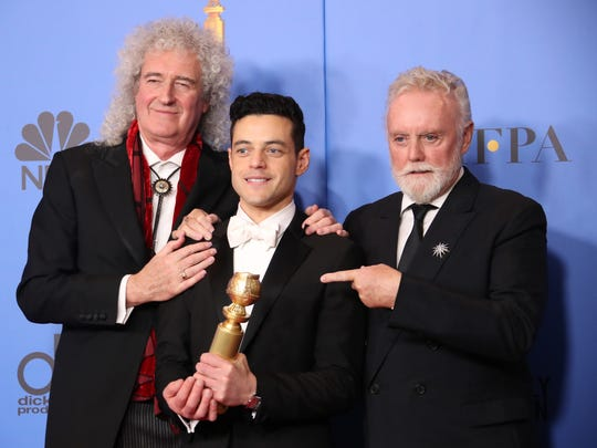 "Brian May, left, and Roger Taylor, right, of Queen, and Rami Malek pose in the press room with the award for best motion picture, drama for ""Bohemian Rhapsody"" at the 76th annual Golden Globe Awards."