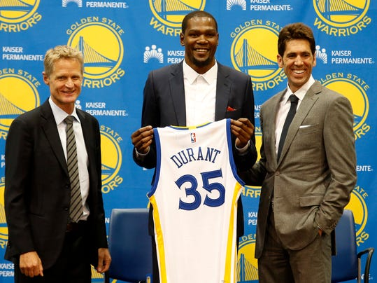FILE - In this July 7, 2016, file photo, Golden State Warriors' newest player Kevin Durant, center, joins head coach Steve Kerr, left and general manager Bob Myers during a news conference at the NBA basketball team's practice facility in Oakland, Calif. Myers has blended a thoughtful, hands-on, hands-off approach with the Golden State Warriors to make him one of the best general managers in sports. (AP Photo/Beck Diefenbach, File)