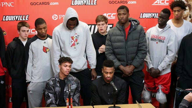 Louisville's Damion Lee, bottom left, and Trey Lewis, bottom right, are joined by the entire team at a press conference to discuss the program's post season ban.   Feb. 5, 2016