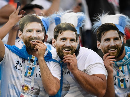 Fanáticos de Lionel messi posan con máscaras del astro culé.