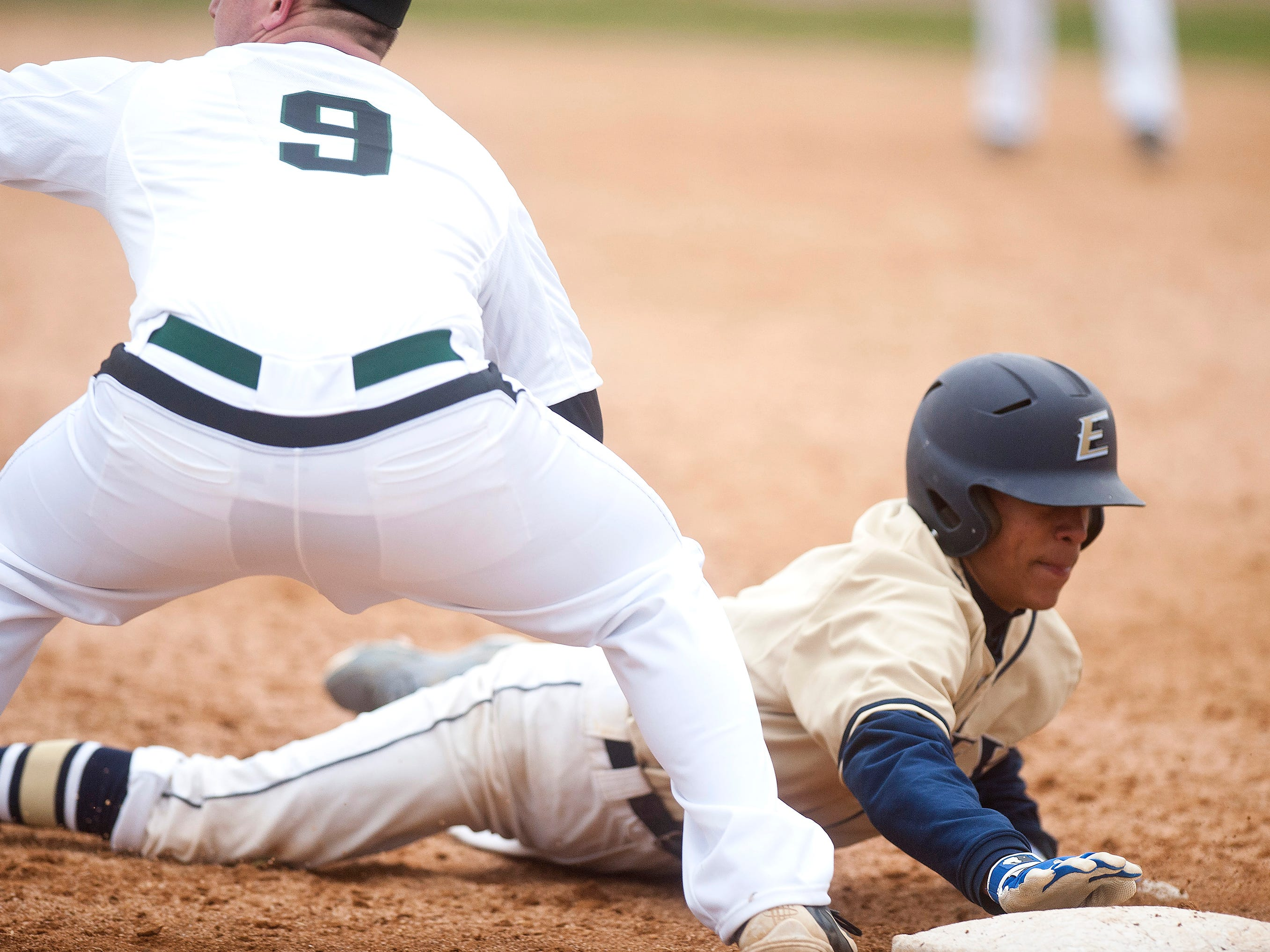 Essex's Elijah Baez, right, slides back into first base to avoid the tag of Rice's John Boardman during Friday's game in South Burlington.