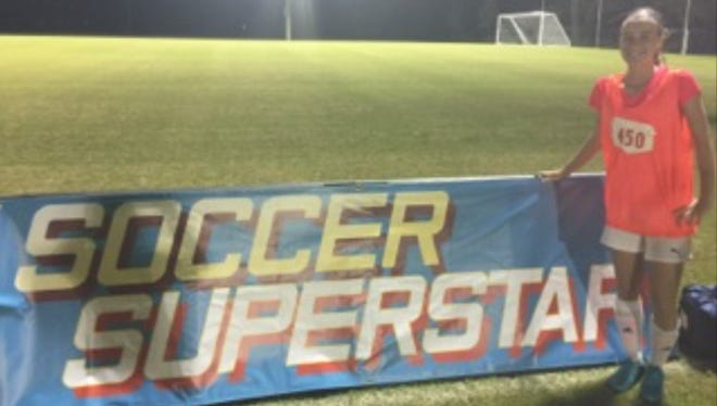 Estero sophomore Marin Yeagle, 15, stands in front of the sign for Soccer Superstar, the reality television series she was a part of in April on NickToons.