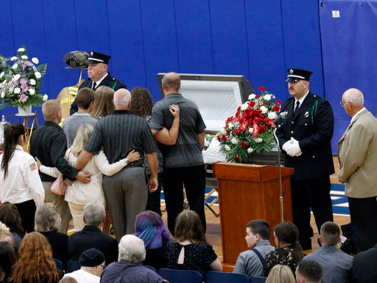 Mourners line up in front of a casket containing Joseph