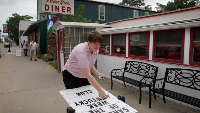 At top, Carrie Ahearn puts the daily specials on the sign in front of the Penn Yan Diner that she owns and runs with her husband, Sean. The diner suffered heavy damage in the May flood but was open by Memorial Day weekend. At bottom left, Jacob's Brook is at lower levels after it flooded a house on its banks. At bottom right, Jim and Sarah Babcock are working on their house that had 6 feet of water on the first floor.