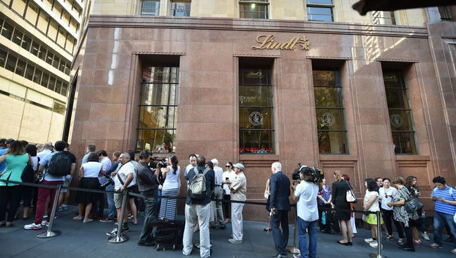 People line up outside the Lindt Cafe in Sydney for its reopening on March 20, 2015, three months after a fatal siege by a gunman who held customers and staff hostage.