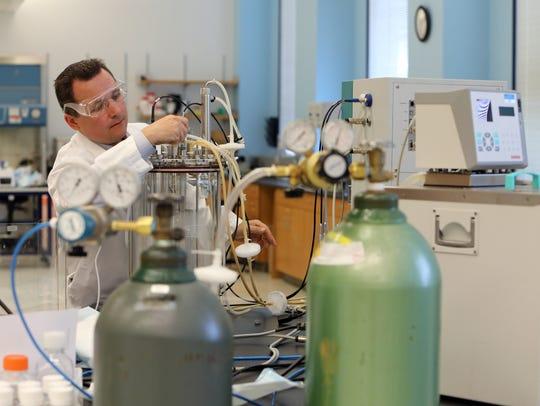 Demetrius Matassov prepares a bioreactor for vaccine